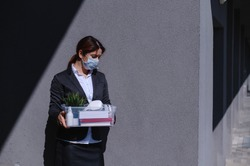 Unhappy unemployed woman in a protective mask is standing with a box of personal belongings against a gray wall. Business lady fired. The global economic crisis. Job cuts due to company bankruptcy.