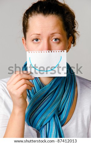 Stock Photo unhappy woman is holding paper with drawn smile