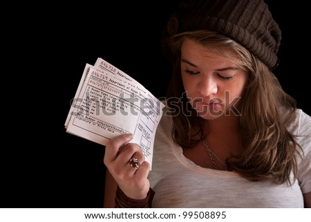 Unhappy woman with food coupons over black background