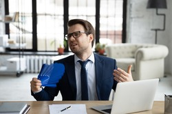 Unhappy young Caucasian businessman sit in office work on laptop wave with hand fan suffer from heatstroke. Unwell male employee struggle with hot weather breathe fresh air form waver.