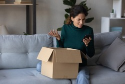 Unhappy young Caucasian woman look at cellphone screen dissatisfied with online order shopping on internet. Upset female use smartphone unpack box get wrong or damaged packaged. Bad delivery concept.