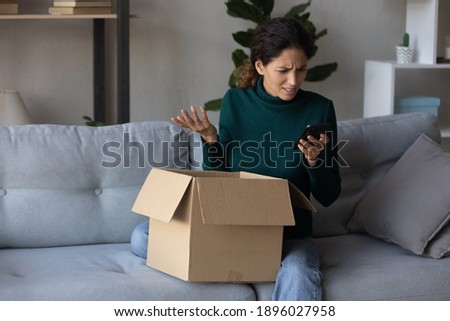Unhappy young Caucasian woman look at cellphone screen dissatisfied with online order shopping on internet. Upset female use smartphone unpack box get wrong or damaged packaged. Bad delivery concept. Stock foto ©