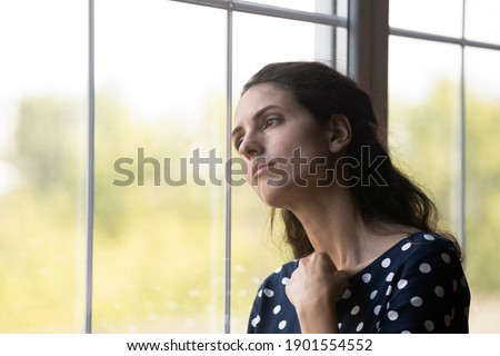 Unhappy young Caucasian woman look in window distance mourn or yearn, feel sad lonely at home. Upset distressed millennial female loner quarantine alone indoors. Solitude, loneliness concept. Stock photo ©