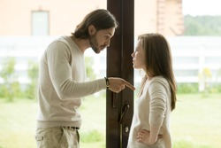 Unhappy young couple arguing standing at house door, angry husband pointing at wife blaming her of problems, conflicts in marriage, bad relationships, man and woman having quarrel or disagreement