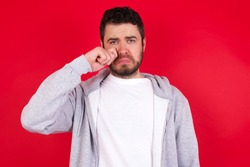 Unhappy young handsome caucasian man in sports clothes against red wall crying while posing at camera whipping tears with hand.
