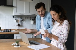 Unhappy young man and woman frustrated by mistake or error when paying bills on computer online. Stunned couple confused by debt calculating family household financial expenditures at home.