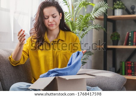 Unhappy young mixed race girl with cardboard box dissatisfied with wrong item delivery