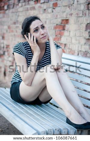 Unhappy young woman crying while talking on the phone - stock photo