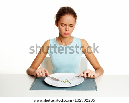 Unhappy young woman dieting with peas and leeks, isolated against white