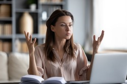 Unhappy young woman looking at laptop screen, irritated by bad gadget work, low internet connection, working remotely at home. Stressed attractive lady annoyed by hard work task or system crash.