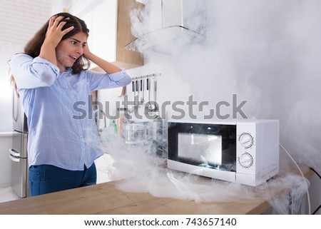 Unhappy Young Woman Looking At Smoke Emitting Through Microwave Oven In Kitchen #743657140