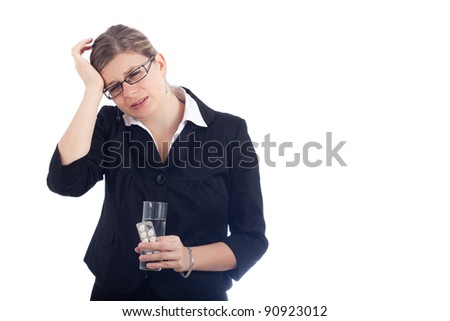 Unhappy young woman with headache holding glass with water and painkillers. Isolated on white background.