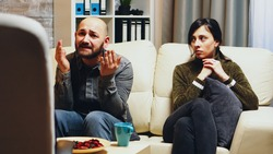 Unhappy young woman with husband at couple therapy. Relationship psychoanalyst.
