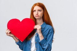 Unhapy brokenhearted cute redhead girl, sulking and looking up uneasy, distressed holding big red valentines day heart, was rejected, showed her feelings standing white background
