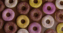 unhealthy but tempting sugary dessert - high angle view of yummy and delicious chocolate and colored icing donuts stack with sprinkles  in calories and sugar abuse nutrition concept