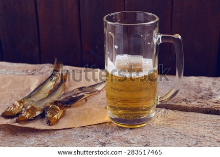 Unhealthy diet, alcoholism. A glass of beer and fish. Beer and snacks. Food and beverage. Appetite. An evening in the pub. Salty smoked fish and half-empty glass of light beer.