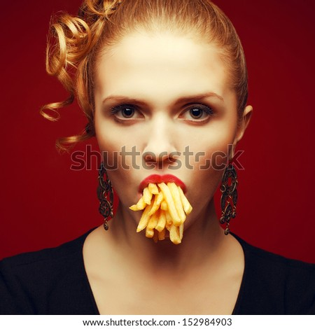 Unhealthy eating. Junk food concept. Arty portrait of fashionable young woman holding (eating) fried potato in her mouth and posing over red background. Close up. Studio shot