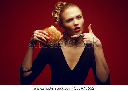 Unhealthy eating. Junk food concept. Guilty pleasure. Portrait of a fashionable model holding burger and pointing on it with index finger. Perfect accessories, hair, skin, make-up and manicure.
