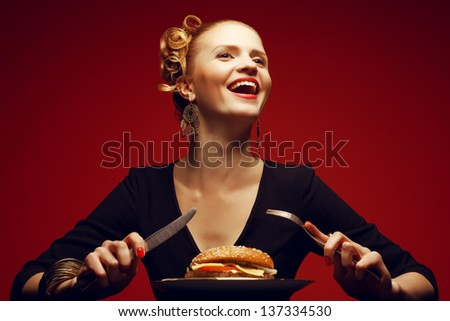 Unhealthy eating. Junk food concept. Portrait of a happy fashionable young woman holding fork and knife and going to eat burger. Perfect hair, skin, make-up and manicure. Copy-space. Studio shot