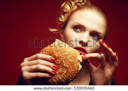 Unhealthy eating. Junk food concept. Portrait of fashionable young woman holding burger and posing over red background. Close up. Copy-space. Perfect hair, skin, make-up and manicure. Studio shot