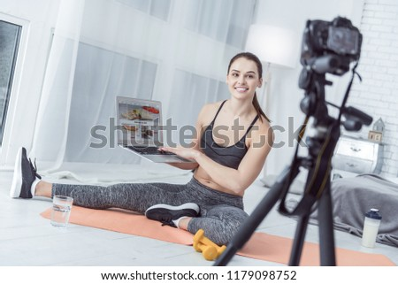 Unhealthy food. Cheerful delighted woman smiling while showing pictures of unhealthy food on her laptop