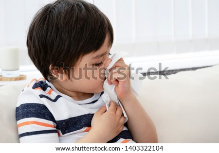 Unhealthy kid blowing nose into tissue, Child suffering from running nose or sneezing , A boy catches a cold when season change, childhood wiping nose with tissue #1403322104