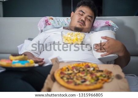 Unhealthy lifestyle concept: Asian obese man eating junk foods during sleeping on the bed #1315966805