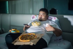 Unhealthy lifestyle concept: Asian obese man eating junk foods while watching TV in bed before sleep