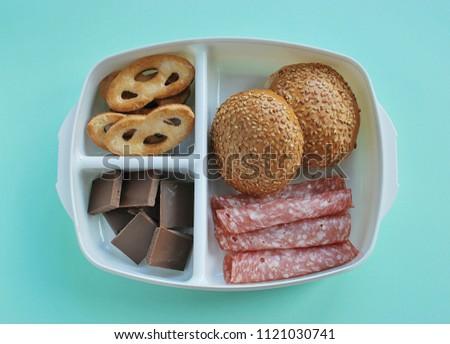 Unhealthy lunchbox. School lunch box with unhealthy food.