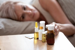 Unhealthy mature woman lying in bed, taking medicine from cold or insomnia, unhappy older female suffering from flu or seasonal fever, treatment concept, pills and meds on bedside table close up