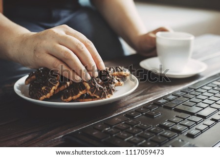 Unhealthy snack at work time. Woman eating chocolate cookies and drinking coffee at workplace. High calorie, fattening junk food, weight gain