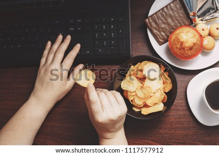 Unhealthy snack at workplace. Hands of woman working at computer and taking chips from the bowl. Bad habits, junk food, high calorie eating, weight gain and lifestyle concept Photo stock ©