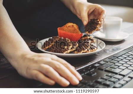 Unhealthy snack, compulsive overeating, mindless snacking, junk food. Woman eating chocolate cookies and drinking coffee at workplace.