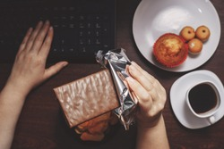 Unhealthy snack. Woman eating chocolate and sugary food at workplace. Brain work improvement during hard work, sugar addiction, lifestyle, weight gain, dietary, healthcare and medical concept.