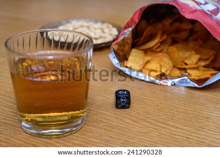 unhealthy snacks on table with skull dice - stock photo