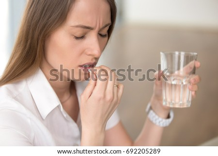 Unhealthy woman with pained facial expression feels unwell, suffering from migraine headache, takes pill analgetic medication to relieve pain, stressed lady holds tablet and glass of water, headshot