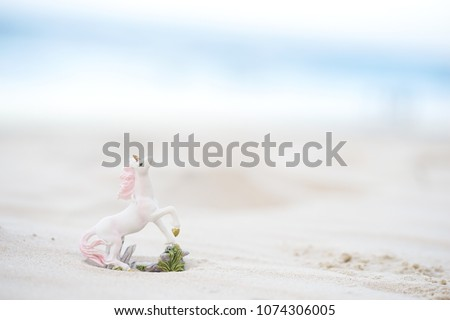 Unicorn. A miniature of unicorn by the beach with shallow depth of field, soft focus and dreamy effect for background and copy space.