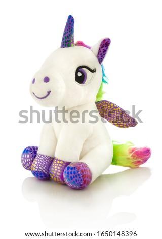 Unicorn plush toy. Isolated on white background with shadow reflection. Unicorn plaything on white reflective underlay. Studio shot. Closeup shot.