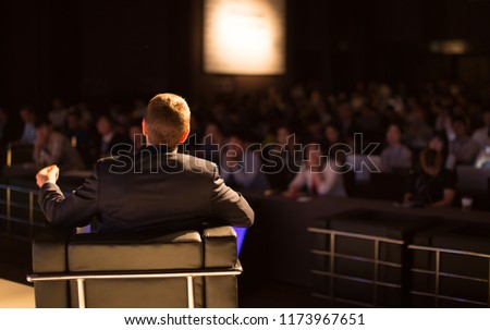 Unidentifiable Businessman on Stage Wearing a Suit with Hand Up Presenting to Blurred Audience at Conference Hall Tech Presentation. Technology Manager Education Lecture #1173967651