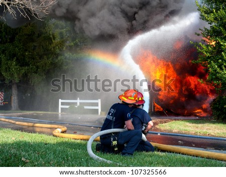 unidentifiable firefighters battling a house fire and creating a rainbow