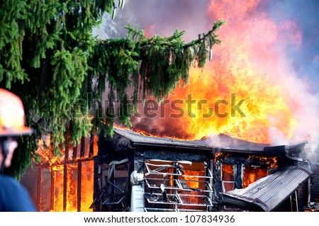 unidentifiable fireman looking on as house burns