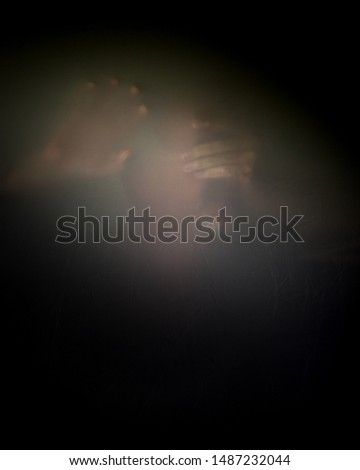 Unidentifiable mature male with mustache goatee a hand over eyes behind veil or screen, expressing anguish fear depression mental health psychological suffering grieving copy space vertical photo