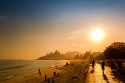 Unidentifiable silhouettes enjoy late afternoon sun rays on Ipanema beach in Rio de Janeiro, Brazil. Ipanema is one of the most expensive places to live in Rio