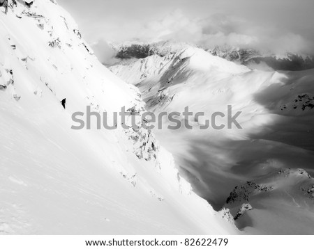 Unidentifiable skier descends a steep mountain in Alaska