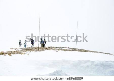 Unidentifiable Snowboarders Hiking Across a Frozen Landscape