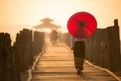 Unidentified Burmese woman holding traditional red umbrella and walking on U Bein Bridge