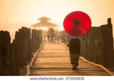 Unidentified Burmese woman holding traditional red umbrella and walking on U Bein Bridge #375020818