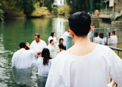 Unidentified Christian pilgrims during mass baptism ceremony at the Jordan River in North Israel (Yardenit Baptismal Site). In Christian tradition, Jesus was baptised in the River Jordan