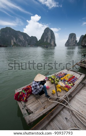 Unidentified female fruit seller sells various types of fruits on boat in Halong Bay, Vietnam