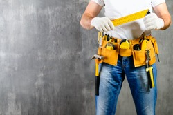 unidentified handyman standing with a tool belt with construction tools and holding a ruler against grey background. DIY tools and manual work concept